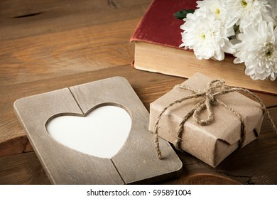 Gift box, old book, heart shaped frame and flower on wooden table