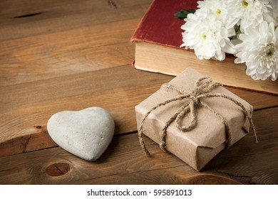 Gift box, old book, heart and flower on wooden table