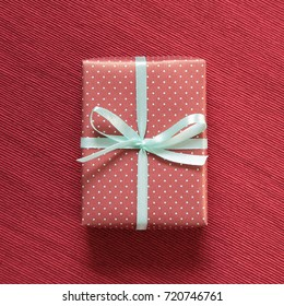 Gift box on red fabric background
