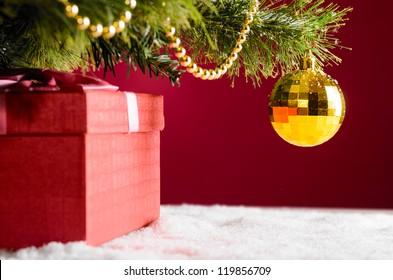 gift box on snow under christmas tree