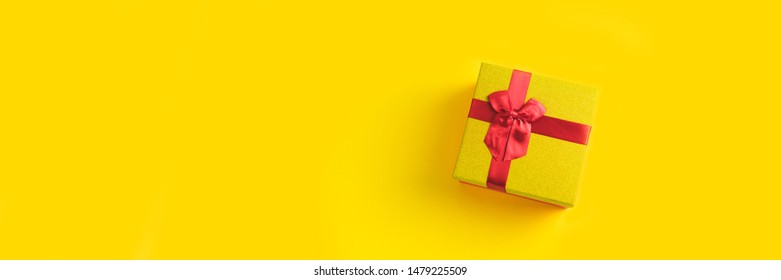 Gift box on sunny yellow background. The concept of the New Year, Christmas, Birthday, Anniversary. Top view. Flatlay