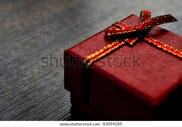 Gift box on table.  Use it in the luxury gift certificate background or in a birthday, valentine or christmas card design.