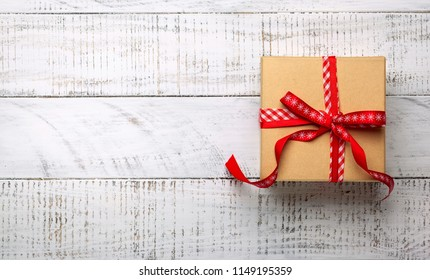 Gift box on white wooden background. Top view with copy-space