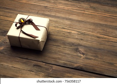 Gift Box on Wood Table, Wrapped Vintage Paper Present With Bow Lying on Brown Wooden Planks