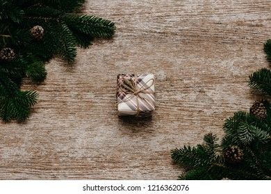 Gift box on the wooden table beside spruce branches. christmas concept. Top view