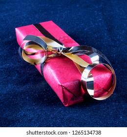 Gift box over black background, square image
