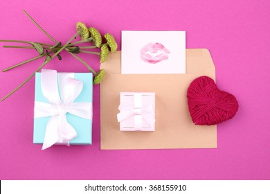gift box (package) with blank gift tag on pink background and flowers, handmade heart.