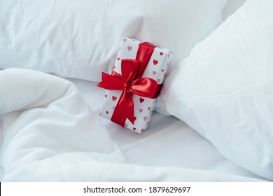 Gift box packed and decorated with a bow on the bed. Valentine's day gift. - Shutterstock ID 1879629697