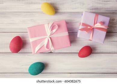 Gift box and painted eggs over wooden background