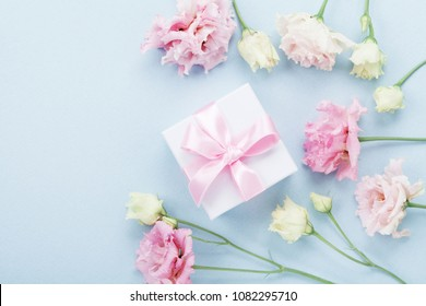 Gift box and pastel flowers for Mothers day on blue table top view. Flat lay style.