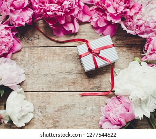 Gift box and peony flowers/top view