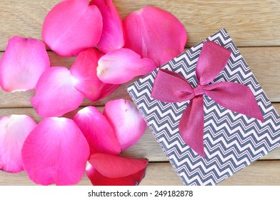 gift box and petal of rose on wooden background
