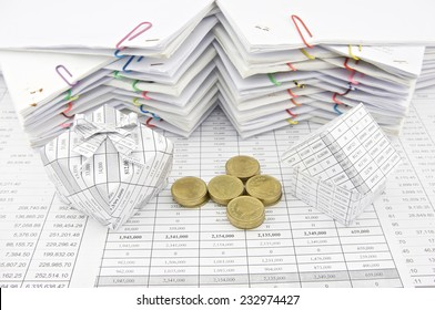 Gift box pile gold coin and house place on finance account with pile of paperwork as background. Stack of paperwork is high as work hard. Business and finance concepts rich and successful photography.
