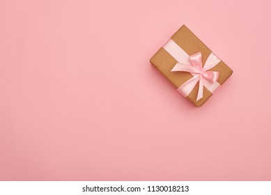Gift box with pink bow placed at the right corner on pink flatla