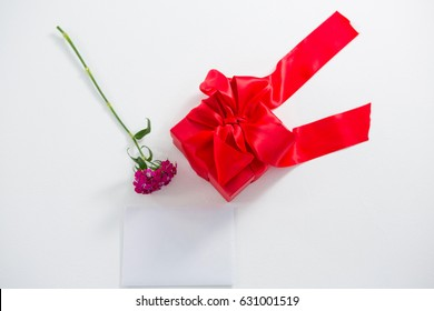 Gift box and pink flower with blank paper on white background