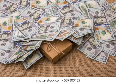 Gift box placed under  spread US dollar banknotes