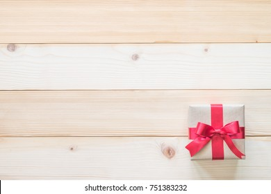 Gift box present with red bow ribbon and brown krafts wrapping paper on white pine wood backdrop for Christmas boxing day, winter xmas holiday seasonal celebration and wedding present background