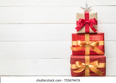 Gift box present stack in Christmas tree shape with red-gold luxury ribbon, star top on white pine wood backdrop for Xmas boxing day and winter holiday seasonal celebration background
