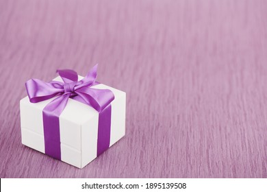 Gift box with purple bow on pink background, shallow depth of sharpness