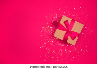 Gift box with red bow on festive bright pink background with golden sparkles around and copyspace for your text. Flat lay style. Christmas, New Year, Valentines Day or birthday celebration concept