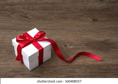 gift box with red bow on rustic table, christmas or another celebration