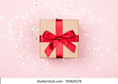 Gift box with red bow on pink background with delicate holographic sparkles.