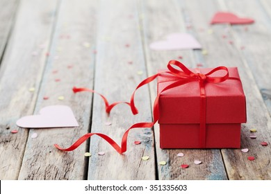 Gift box with red bow ribbon and paper heart on wooden table for Valentines day.