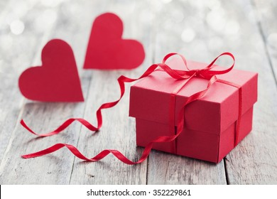 Gift box with red bow ribbon and two paper heart on wooden background for Valentines day.