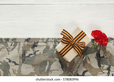 Gift box with red carnation and st george ribbons on the khaki background. Defender of the Fatherland Day