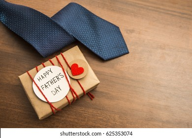 Gift box with red heart and ribbon, blue tie and Father's day card . Striped tie near present box. Best quality gifts for dads. Happy father's day idea, sign, symbol. holiday background