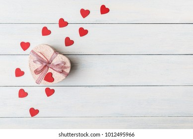 Gift box with red hearts on light wooden background