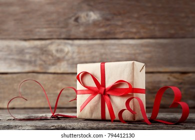 Gift box with red hearts on wooden table