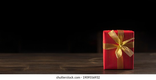 Gift box in a red package with a bow. On a wooden table. Surprise.