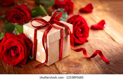 Gift box with red ribbon bow and red roses. Festive concept for Valentine's day, Mother's day or birthday.