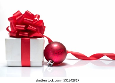 Gift box with red ribbon bow and christmas ball on white background with copy space