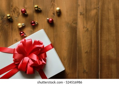 Gift box with red ribbon and christmas balls on wood background.Top view with copy space