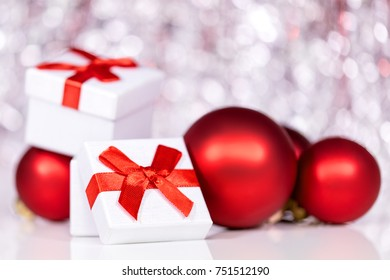 Gift box with red ribbon and christmas balls, festive shiny background