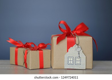 Gift box with red ribbon and house model with keys on black  background, Gift new home and Real estate concept