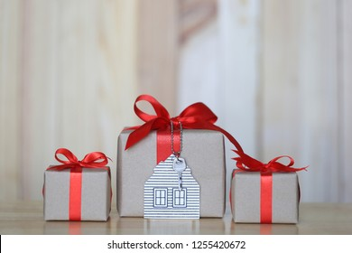 Gift box with red ribbon and house model with keys on wooder background, Gift new home and Real estate concept