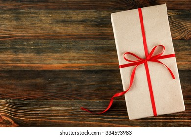 Gift box with red ribbon on wood background