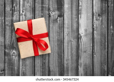 Gift box with red ribbon on black and white wooden background