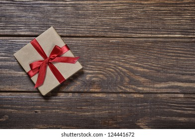 Gift box with red ribbon over wooden background