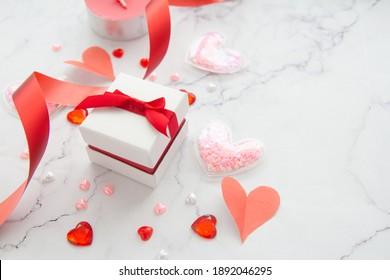 Geschenkbox mit rotem Band und Papierherz auf weißem Marmor Hintergrund für den Valentinstag