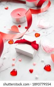 Geschenkbox mit rotem Band und Papierherz auf weißem Marmor Hintergrund für den Valentinstag. Das Konzept von Urlaub und Liebe.