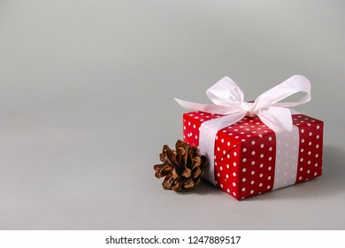 Gift box in red wrapping paper with white polka dots, white bow and pine cone on grey background with copy space