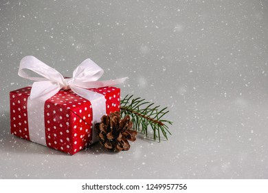 Gift box in red wrapping paper with white polka dots, white bow and pine cone under snow on grey background with copy space