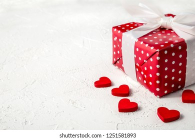 Gift box in red wrapping paper with white polka dots, white bow and wooden red hearts on white textured background with copy space. Valentine's day. Love and romance concept