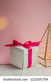 gift box with ribbon on minimalistic pink background and florarium glass geometric terrarium with reed flowers. reeds common bulrush