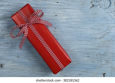 Gift box with ribbon on old wooden table