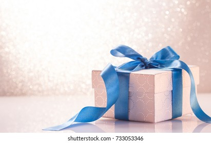 Gift box with ribbon on white glitter background